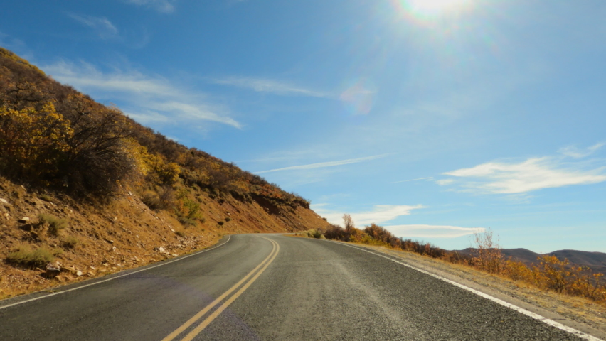 Scenic fall autumn drive high mountains Utah POV 4K. Beautiful autumn fall colors along Wasatch Mountains. Valley landscape with road and colorful fall trees. Rural farming community road. | Shutterstock HD Video #1061538094