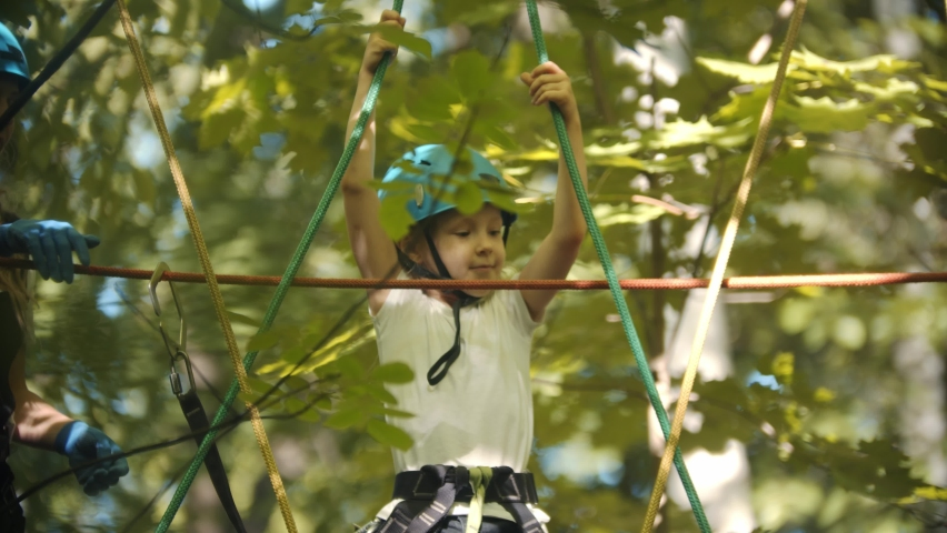 A little girl walking on a rope bridge between the trees with protective hook attached to the rope | Shutterstock HD Video #1061539039