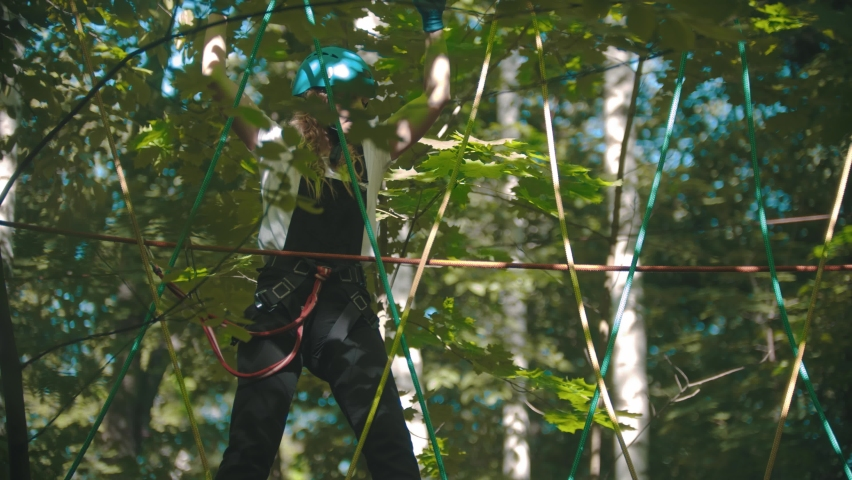 A woman walks on the rope between trees at altitude - extreme rope adventure | Shutterstock HD Video #1061539042