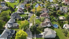 Overhead aerial view of colorful autumn trees, residential houses and yards with drainage pond along suburban street in Chicago area. Midwest USA