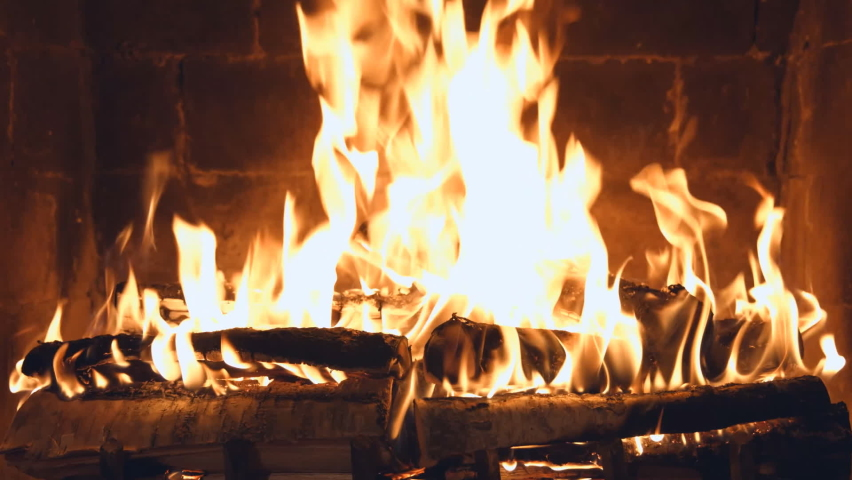 Fire is burning in the fireplace. Hearth. Warmth and home comfort. Flames of a country house.