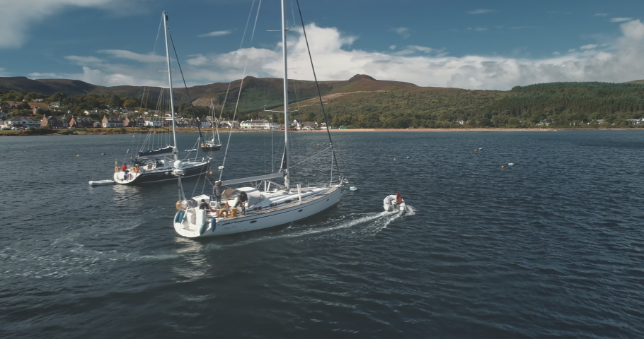 Closeup of motor boat sails at yachts on ocean bay aerial. Sunlight over serene seascape with water transport. Green mountain shore of Brodick harbor, Arran island, Scotland. Cinematic soft light | Shutterstock HD Video #1061544499
