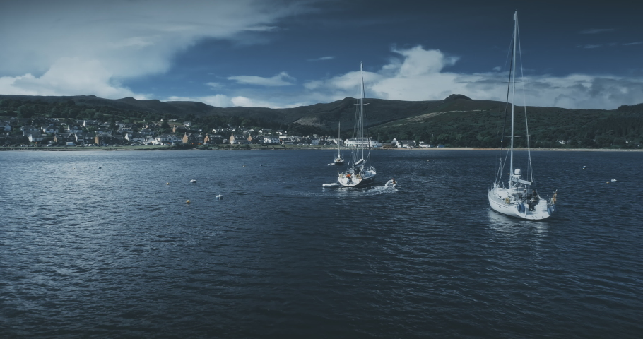 Sailing boats at ocean bay aerial. Summer cruise on luxury yachts with passengers. Dramatic Scotland sea coast of green mountains island of Arran with water transport at cinematic drone shot | Shutterstock HD Video #1061544508