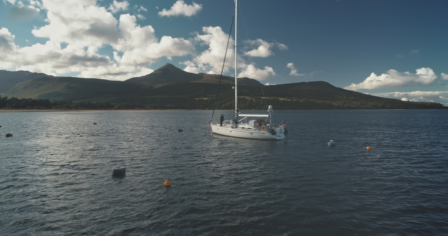 Amazing seascape of ocean bay with yacht aerial. Green mountain island with forest at mist haze. Epic sail boat at sea harbor of Brodick pier, Arran island, Scotland, Europe. Cinematic summer cruise | Shutterstock HD Video #1061544514