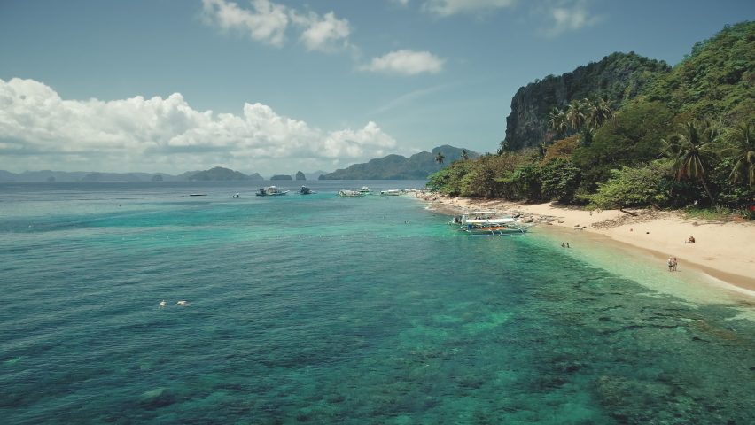 Ocean sand coast with vessels aerial timelapse. Boats and ship at shallow azure water. People rest on sandy beach. Asia tourist landmark on Palawan island, El Nido, Philippines, Asia | Shutterstock HD Video #1061544517