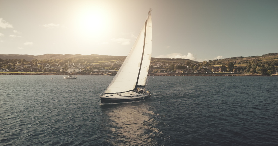 Racing yacht at sun reflection on sea bay aerial. Nobody nature seascape with sail boat at sunshine. Port town cityscape at green highland with mountain shore landscape. Cinematic drone shot | Shutterstock HD Video #1061544520