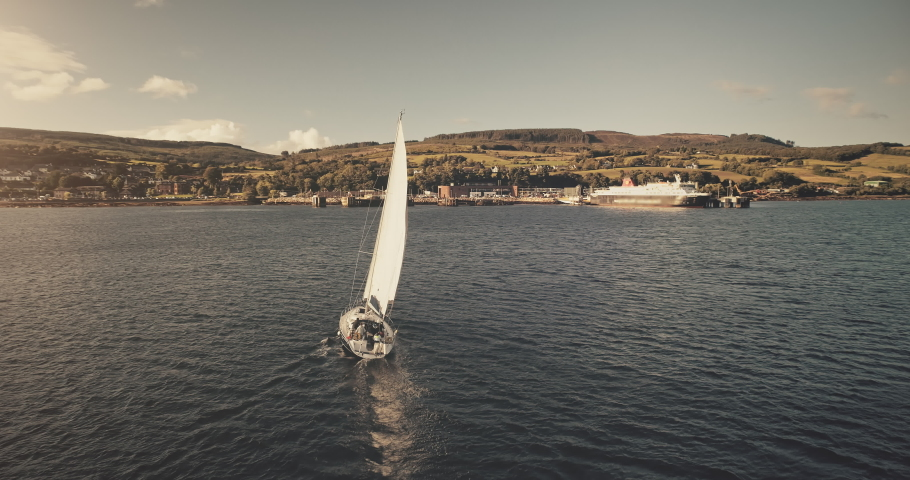 Aerial view of sun light on sail boat at ocean bay reflection. Highland sea coast with forest and mounts at bright sunlight. Nobody nature seascape at Brodick harbor with luxury yachts cinematic shot | Shutterstock HD Video #1061544523