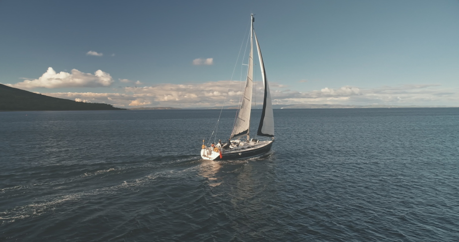 Slow motion of luxury yacht sailing at ocean bay aerial. Passenger sailboat race at open sea near Arran Island, Scotland, Europe. Epic summer cruise on boat at cinematic soft light drone shot | Shutterstock HD Video #1061544529