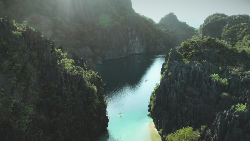 Green cliff island shore of sea bay aerial. Boats on water surface at rock coast. Tropic forest on mountainous isles of Palawan, El Nido, Philippine archipelago. Amazing summer cruise scene drone shot | Shutterstock HD Video #1061544574