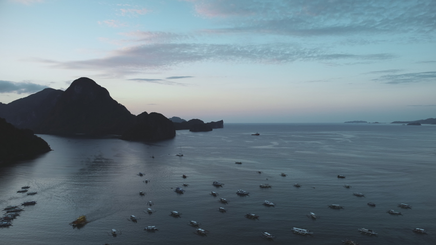 Slow motion of mountain island silhouette at pier with boats, ships, vessels aerial. Majestic nobody seascape at mountainous islets of El Nido, Philippines, Visayas archipelago cinematic drone shot | Shutterstock HD Video #1061544580