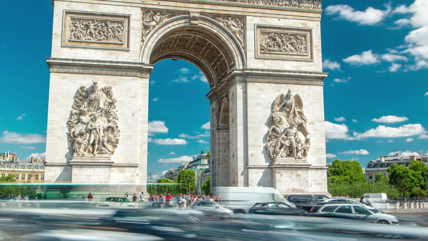 The Arc de Triomphe (Triumphal Arch of the Star) timelapse is famous monument in Paris, standing at the western end of the Champs-Elyseees. Traffic on circle road. Blue cloudy sky at summer day