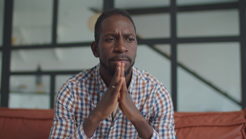 Portrait of pensive handsome african man in deep thoughts sitting on sofa in domestic interior, thinking about problems and solutions, making hard decisions, expressing worry and unconfident.   Shutterstock HD Video #1061546107