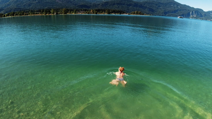 A woman plunges into the beautifully clear alpine lake Wolfgangsee and swims. A beautiful sunny day in the mountains. Alps, Austria - 05.12.2019 Royalty-Free Stock Footage #1061549560