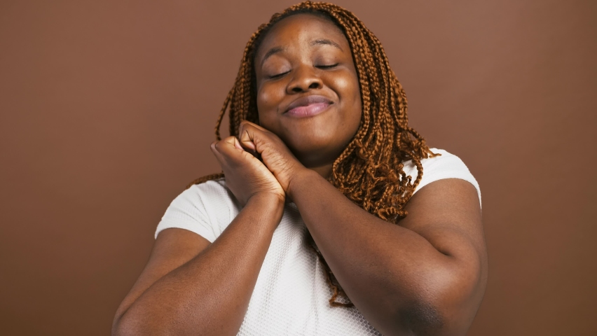 Grateful black woman clasping hands and smiling, touched by complement, enjoying greeting, brown studio background
