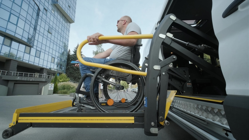 A man in a wheelchair on a lift of a vehicle for people with disabilities. Lifting equipment for people with disabilities - man in wheelchair near the vehicle Royalty-Free Stock Footage #1061563771