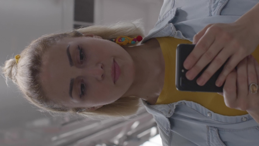 Attractive young woman watching video on smartphone in public transport metro.Video for the vertical story.  Royalty-Free Stock Footage #1061570896
