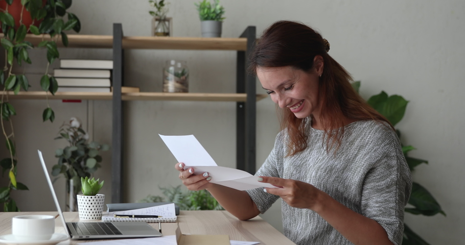 Happy young woman opening paper correspondence letter, reading good news, satisfied with bank loan approval or excited by interesting event invitation, celebrate professional achievement success. Royalty-Free Stock Footage #1061572699