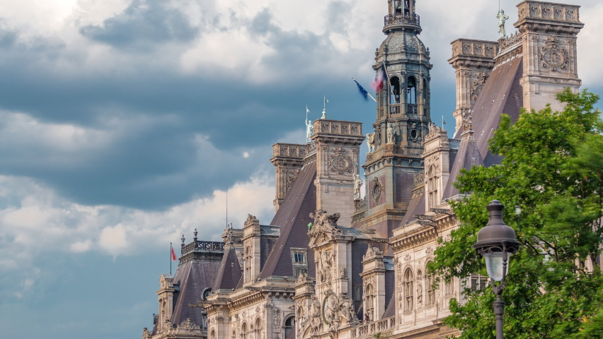 Architecture of The Hotel de Ville City Hall with french flag on tower timelapse, the building housing the local administration of the city of Paris. Cloudy sky at summer day. Close up view