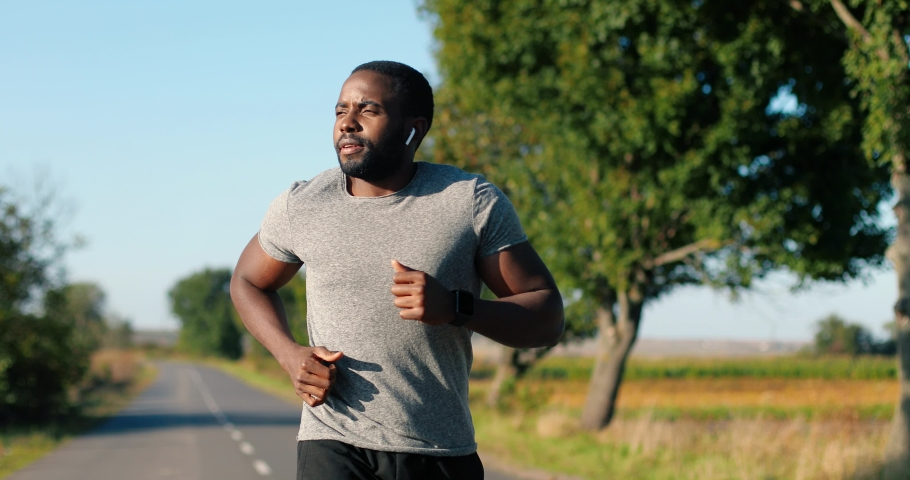 African American handsome strong male jogger in headphones running on road in countryside on summer day. Attractive sporty man jogging outdoors. Sport concept. Sportsman runner. Morning nature. | Shutterstock HD Video #1061593126
