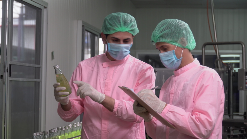 two food scientist worker wearing hairnet and face mask discussing while checking quality control and writing notes of juice bottle in industrial water factory. inspection in line production beverage Royalty-Free Stock Footage #1061593165