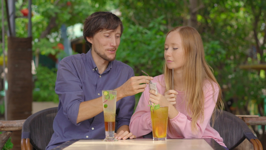 In a cafe young couple have a chat. They drink their drinks using reusabla steel straws. Concept of reducing the use single plastic Royalty-Free Stock Footage #1061593975