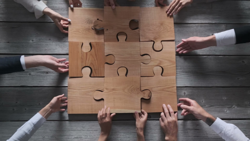 Business people team sitting around meeting table and assembling wooden jigsaw puzzle pieces unity cooperation ideas concept Royalty-Free Stock Footage #1061596747