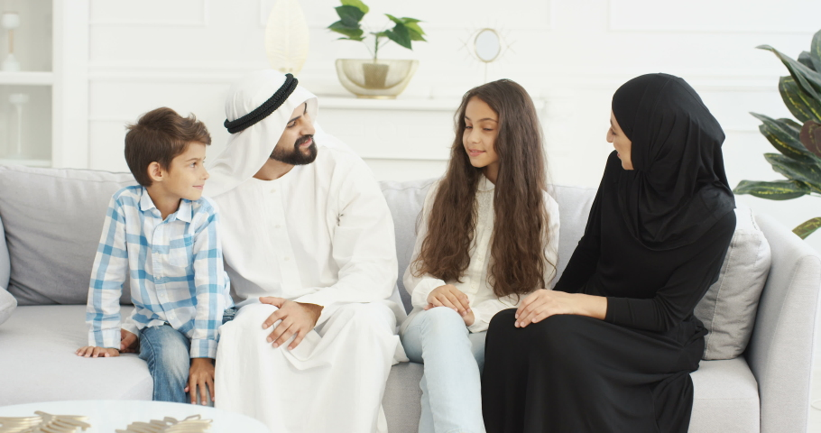 Portrait of cheeful Muslim family with two kids sitting on couch and smiling joyfully to camera. Small cute boy and girl with mother and father at home. Arabian parents with little children hugging. Royalty-Free Stock Footage #1061603233
