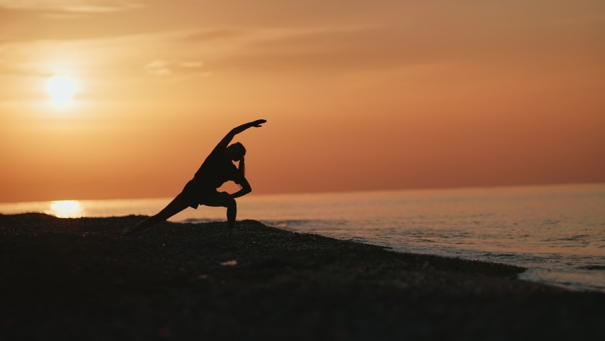 Silhouette of fitness woman practicing asana yoga pose on beach at dramatic sunrise sky. Female doing sports exercise stretching body at seascape morning nature long shot. 4k Dragon RED camera