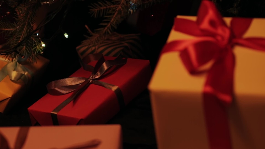 Granddaughter puts a gift under the christmas tree. Beautiful presents under the Christmas tree. New Year interior. Christmas tree, happy holidays. New Year's gift box. Christmas spirit, holidays  | Shutterstock HD Video #1061608300