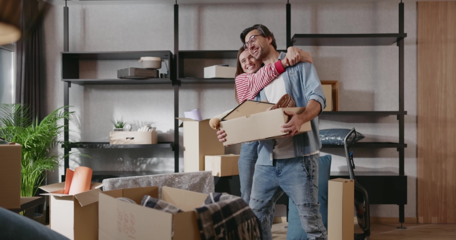 Excited married couple young family moving house bringing unpacking boxes discussing and planning future furniture interior. Cozy apartment. New home. Relocation. Life event. Royalty-Free Stock Footage #1061608780