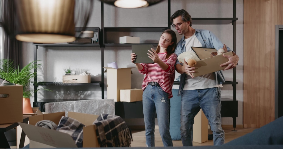 Joyful young couple moving home decorating room using digital tablet pc computer choosing internet future furniture virtual reality objects visualizing new interior. Apartment. Technology.