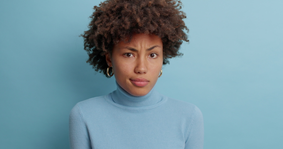 Uncertain clueless woman with Afro hair hesitates about something says no and feels puzzled dressed in casual turtleneck isolated over blue background. Indecisive questioned young female poses indoor Royalty-Free Stock Footage #1061620735