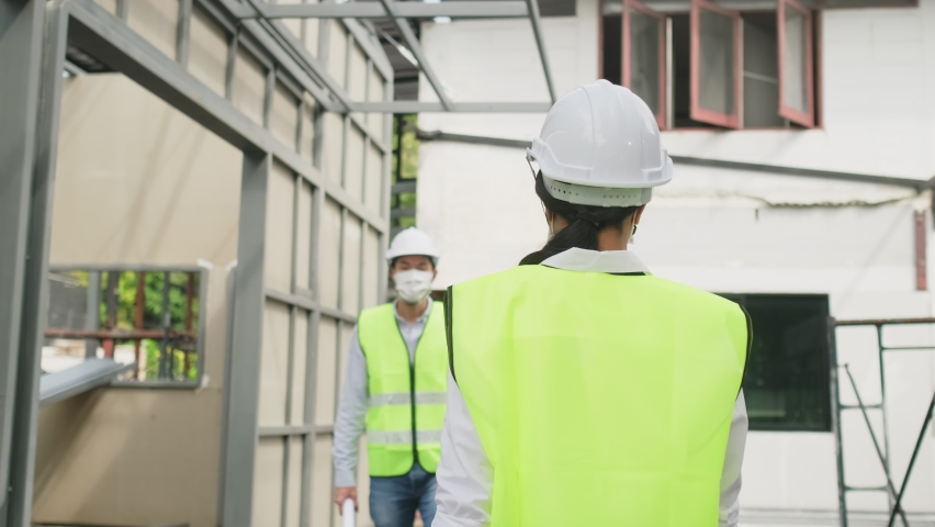 Asian workers people wearing protective face mask onsite of architecture due to covid pandemic crisis. Male and female engineers making elbow touch instead of handshake to avoid coronavirus infection. Royalty-Free Stock Footage #1061623189