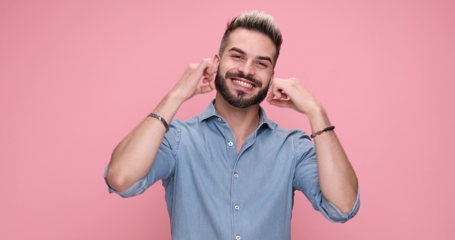 Young casual man pointing at the camer and expanding his smile, giving a thumbs up on pink background
