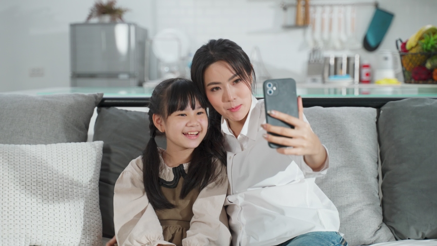 Asian family little kid girl and mother talking in video conference by smartphone together in living room at home with happiness and smile. Happy activity technology lifestyle mobile phone use concept