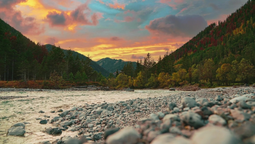 4K UHD Cinemagraph / seamless video loop of a mountain river in the Austrian alps with a vibrant evening sky, close to the German border in autumn. The water is rushing along colorful fall trees.