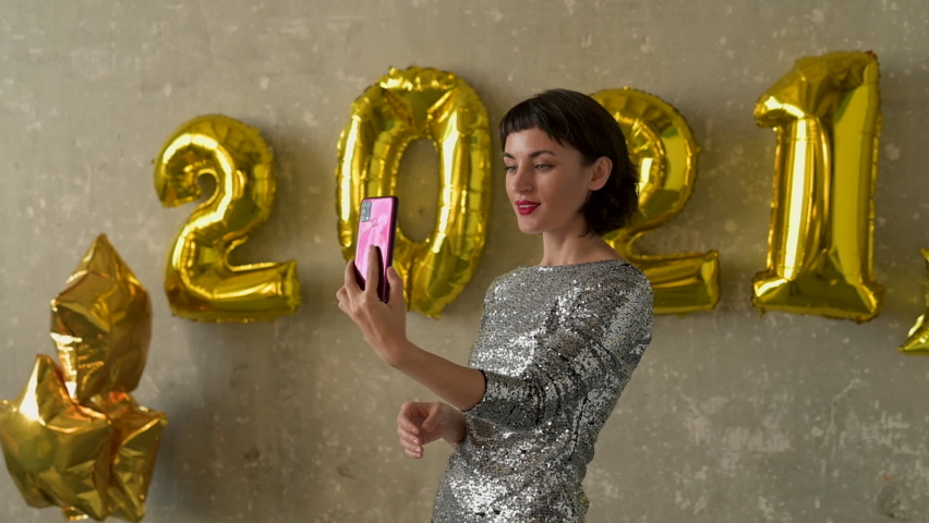 Happy new year 2021. Young pretty woman have a video call holding a phone on New Year's Eve. Female wearing evening dress at glamorous party with golden number-shaped balloons on the wall. Royalty-Free Stock Footage #1061637208