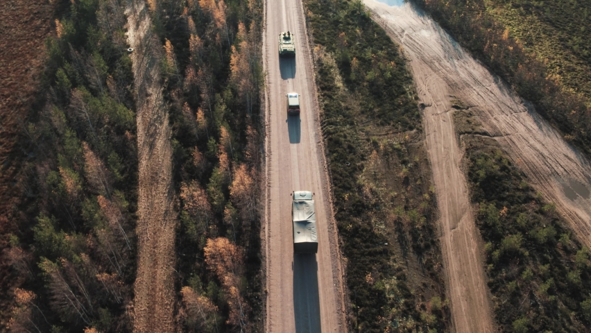 A military convoy is moving along the road. Aerial view.