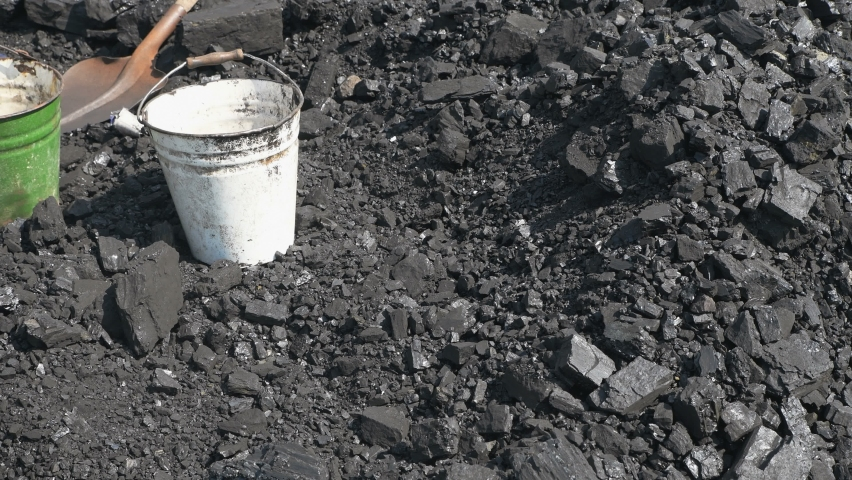 Coal is loaded by workers using shovels. Miner's dust. Stone ore for fuel. Power industry. 4K video.