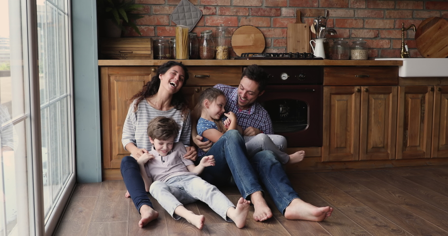 Couple play with kids tickling them feels happy, full family sit barefoot on warm wooden floor with underfloor heat system enjoy weekend at modern house in domestic kitchen. Time with children concept