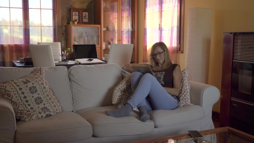 Blond woman using digital tablet at home | Shutterstock HD Video #1061647969