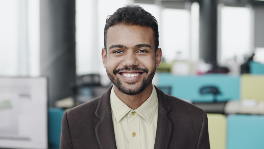 Handsome young businessman smiling in the office. Cheerful self confident man portrait. Business, success, people concept Royalty-Free Stock Footage #1061649802