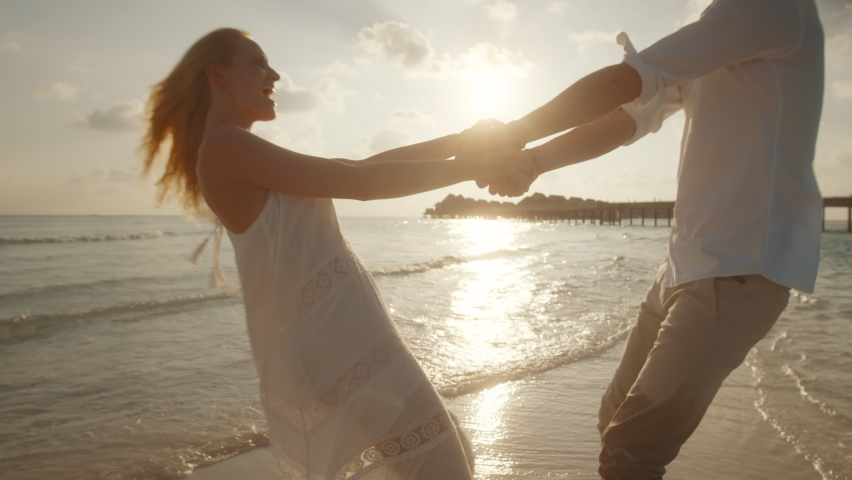 Couple in love holding hands and dancing on the beach. Couple holding hands and moving in circles on the seashore.