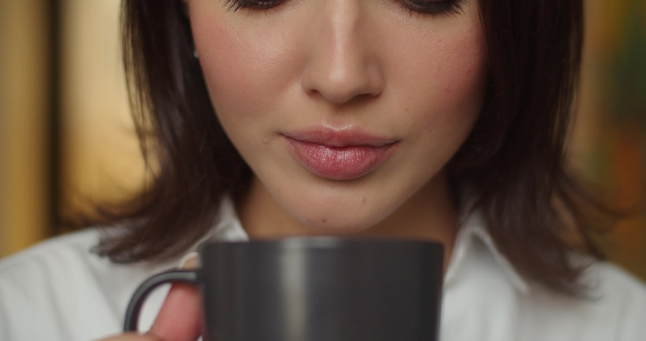 Detailed macro shot of female face drinking hot tea indoors slow motion. Unrecognizable woman with make-up holding cup of coffee close up no face. Lips lipstick facial beauty cosmetics Royalty-Free Stock Footage #1061653222