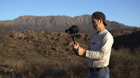 Filmmaker filming video with camera stabilizer on the mountain. Professional cameraman working on film