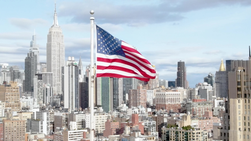 Aerial Orbit of USA flag waiving in the wind with Midtown and Hudson Yards in the background.