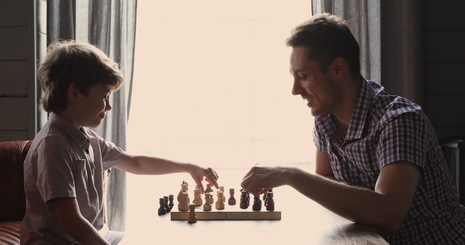 Side view cute little 6s son and young father play chess seated indoor. Concentrated boy develop strategy, planning, foresight skills, engaged in board game with parent at home, entertainment concept | Shutterstock HD Video #1061686555