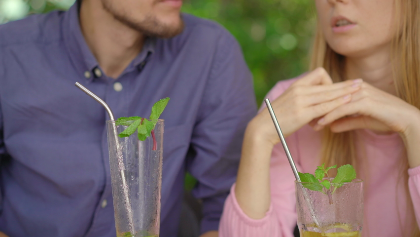 In a cafe young couple have a chat. They drink their drinks using reusabla steel straws. Concept of reducing the use single plastic Royalty-Free Stock Footage #1061687704