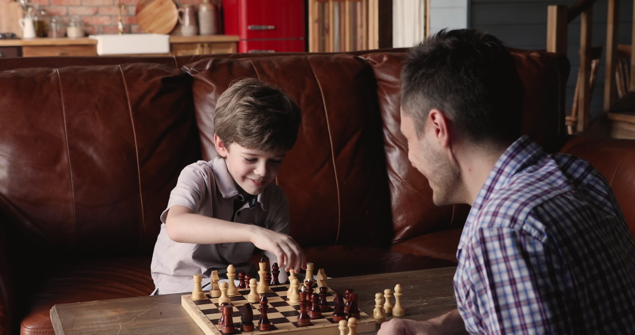 Father and son spending time together at home playing chess, family sit at table opposite of each other making moves enjoy educational game. Parent teach 7s child, leisure activity, brain work concept | Shutterstock HD Video #1061690407