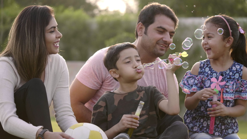 Happy family including mother, father, and two kids are blowing soap bubbles and enjoying the summer holidays in the garden or park. Smiling parents and children are spending leisure time together.